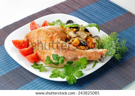 Fried chicken leg with vegetables and greens on a platter - stock photo