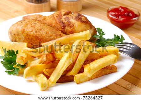 Fried chicken legs with lemon and potato served on the white plate - stock photo