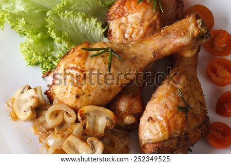 Fried chicken legs with mushrooms on a plate close-up. horizontal view from above  - stock photo
