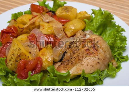 Fried chicken legs with tomato and potato served on the white plate - stock photo