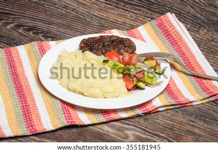 Fried chicken, mashed potatoes and fresh vegetable salad on the napkin