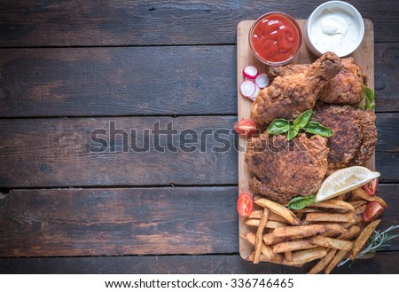 Fried chicken meat with buttermilk and french fries on wooden background with blank space - stock photo