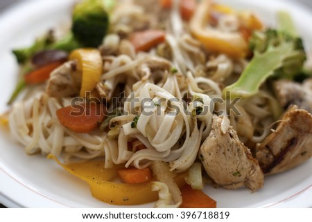 Fried chicken noodles with vegetables broccoli, cabbage, paprika and carrots.