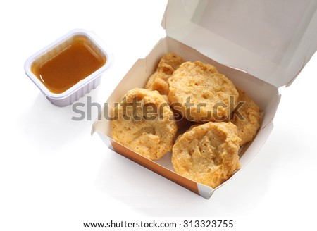 Fried chicken nuggets in box with dressing   - stock photo