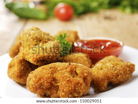 Fried chicken nuggets on the plate on the table with sauce
