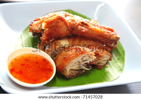 Fried chicken on a banana leaf served with spicy sweet dipping sauce