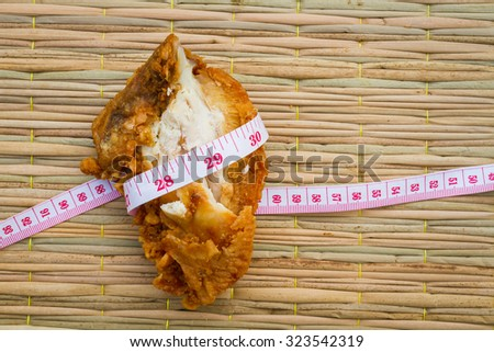 fried chicken on traditional mat with measuring tape, diet concept. - stock photo