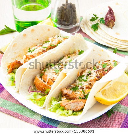 Fried chicken, salad lettuce, carrots and sauce in wheat cake for lunch, delicious Mexican burritos - stock photo