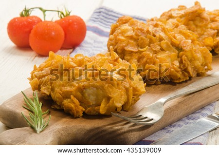 fried chicken thighs coated with corn flakes, rosemary and tomato on wooden board