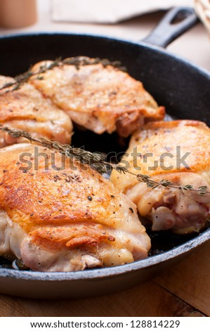 Fried chicken thighs in cast iron pan closeup
