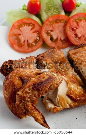 fried chicken wing with vegetables on white background. - stock photo
