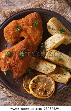 Fried chicken wings dipped in batter closeup with garnish on a plate on the old table. top view of the vertical  - stock photo