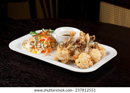 Fried chicken wings garnished with fresh vegetables with Teriyaki sauce - stock photo