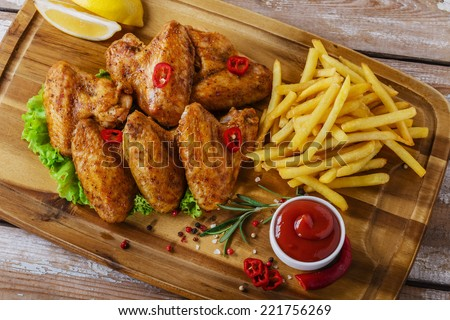 fried chicken wings with red sauce and French fries - stock photo