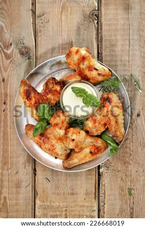 Fried chicken wings with sauce on rustic table, top view - stock photo