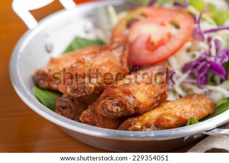 Fried chicken wings with vegetable in steel bowl. - stock photo