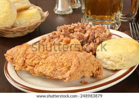 Fried chicken with a biscuit, beans and rice, and a mug of beer