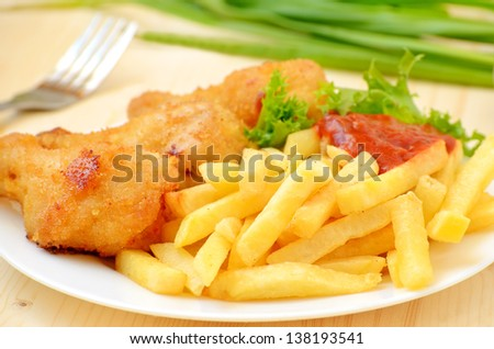 Fried chicken with french fries on the table - stock photo