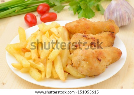 Fried chicken with french fries on wooden table