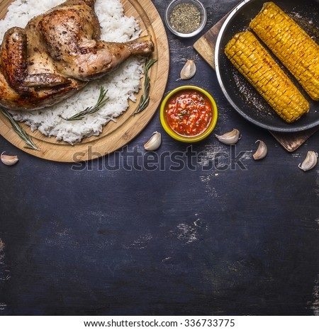 fried chicken with rice on a cutting board, hot sauce, spices, garlic and corn in the pan on dark blue wooden rustic background top view close up place for text  - stock photo
