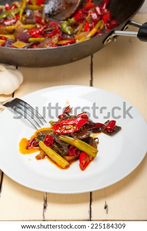 fried chili pepper and vegetable on a iron wok pan - stock photo