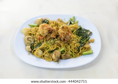 fried chinese egg noodles with seafood, selective focus - stock photo