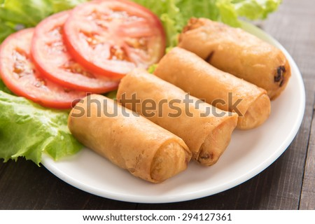 Fried Chinese traditional spring rolls on wooden background.