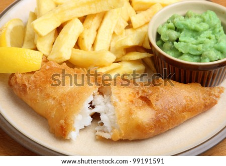 Fried cod fillet with chips and mushy peas. Shallow DoF, focus on the fish. - stock photo