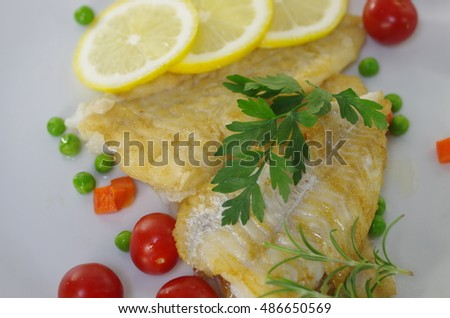 fried cod fish fillet on a plate with parsley and lemon