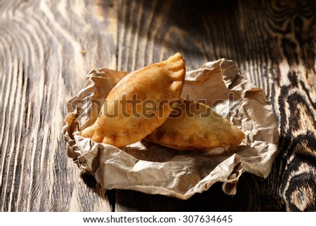 Fried colombian empanadas on wooden table. Savory stuffed patties also known as pastel,pate or pirozhki. Latin takeaway - stock photo