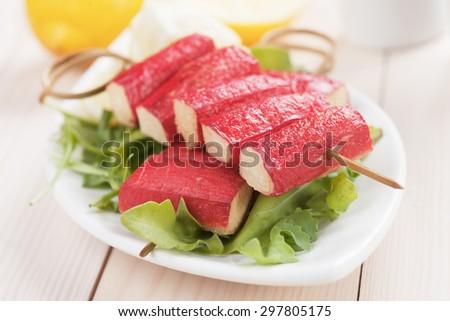 Fried crab sticks (surimi) skewer served over rocket salad - stock photo