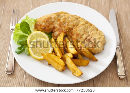 Fried cutlet with potato wedges and salad