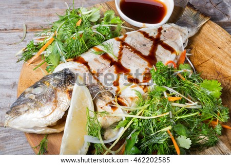 Fried dorado fish served with herbs and soy sauce