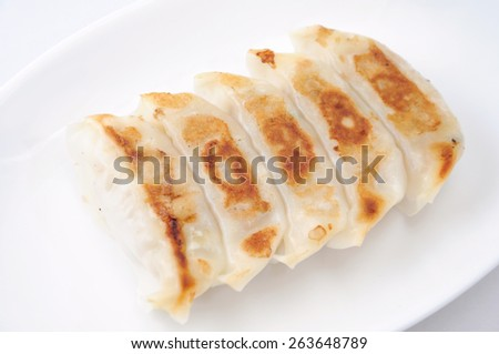 Fried Dumpling Gyoza. Garnished on plate on white background - stock photo