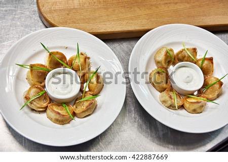Fried dumplings with sour cream sauce in kitchen of restaurant - stock photo