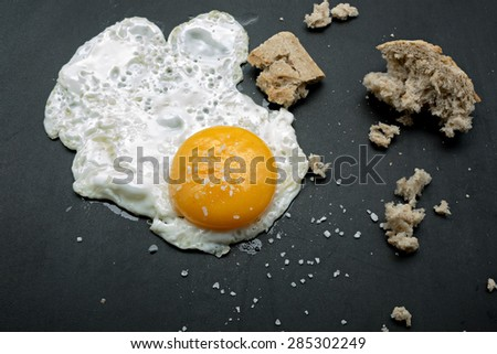 Fried egg and bread on a cast iron griddle - stock photo