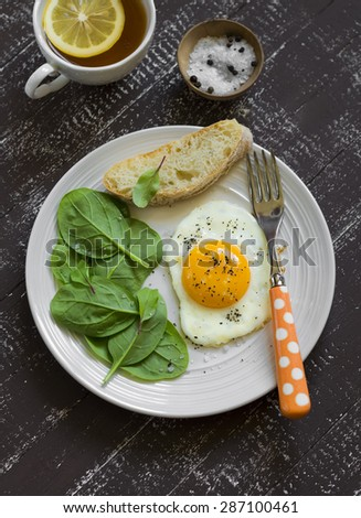 fried egg and fresh spinach on a dark wooden background - stock photo