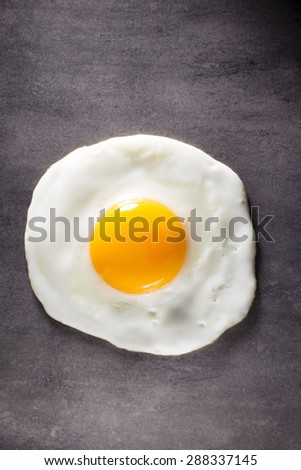 Fried egg and gray background. Studio photograpy.