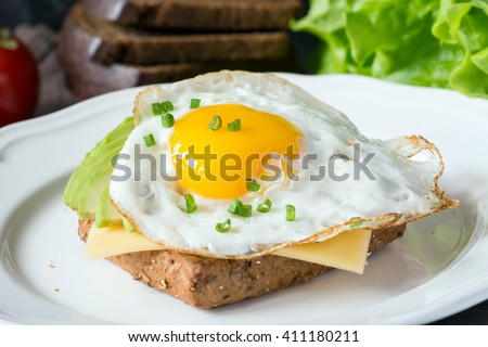 Fried egg, avocado and cheese on whole wheat toast. Delicious and healthy breakfast. Selective focus - stock photo