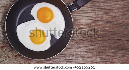 Fried egg in a frying pan on a wooden background. - stock photo
