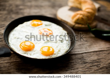 Fried egg in a frying pan on a wooden table - stock photo