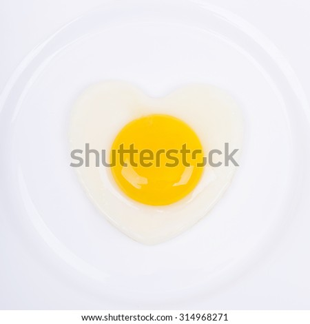 Fried egg in a heart shape in a white plate, selective focus and place for text - stock photo