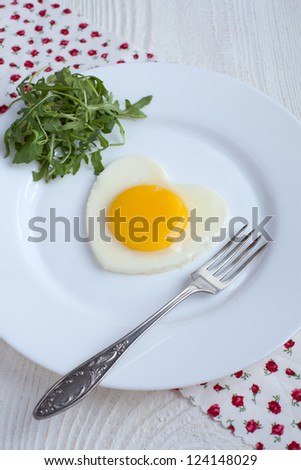 Fried egg in a heart shape with Rocket and fork in a white plate on white background