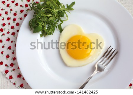 Fried egg in a heart shape with Rocket and fork in a white plate on white table - stock photo
