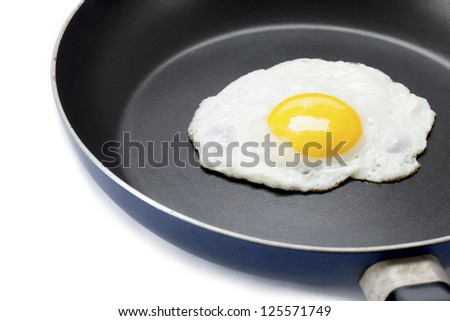 Fried egg in a pan displayed on white background. - stock photo