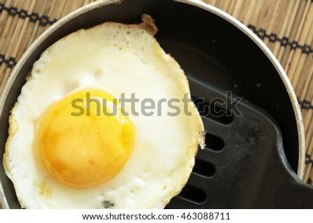 Fried egg in a small saucepan on a tablecloth