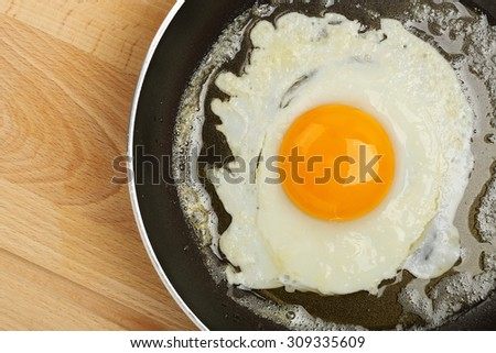 fried egg in frying pan on wooden surface - stock photo