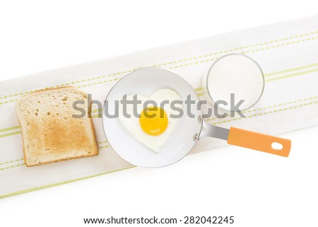 Fried egg in heart shape on pan with toast and milk, top view. I love breakfast. Fresh modern image language. Culinary arts.  - stock photo