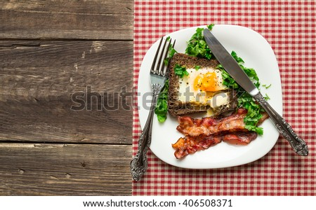 Fried egg in rye bread with bacon and parsley on rustic wooden background. Top view.