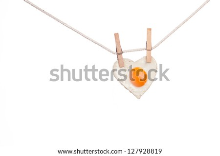 Fried egg in shape of love heart hung from wooden clothes pins or pegs, white background. - stock photo